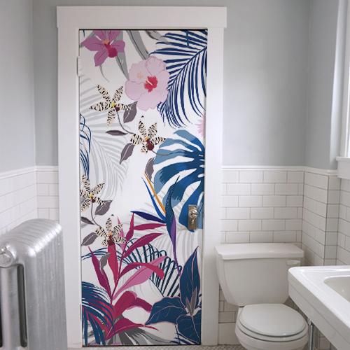 Salle de bain décorée avec un adhésif de porte jungle représentant une végétation exotique rose verte et bleue.