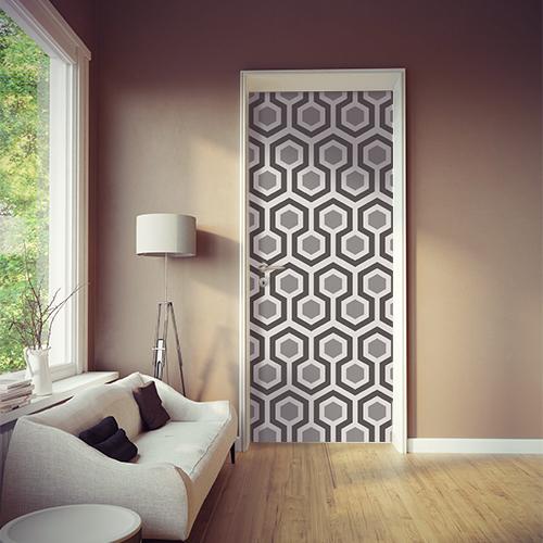 Salon avec porte personnalisée par un sticker de portes nid d'abeille avec décors hexagones gris tendance.