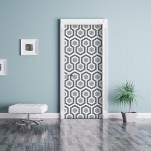 Séjour avec une porte décorée d'un sticker nid d'abeille avec motif hexagones gris.