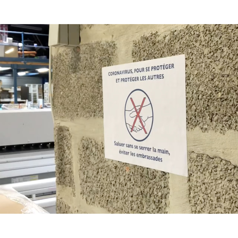 feuilles imprimées gestes barrières sur un mur