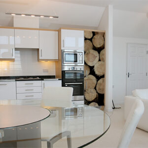 Cuisine de luxe blanche avec un sticker rustique buches de bois sur son grand frigo
