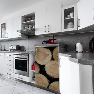 Cuisine tout équipée avec un frigo décoré d'un sticker buches en bois