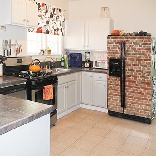 Frigo américian classique dans une cuisine blanche orné d'un sticker déco adhésif imitation briques rouges