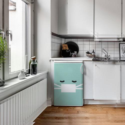 Cuisine moderne blanche et noire avec un sticker smiley malade turquoise collé sur le frigo