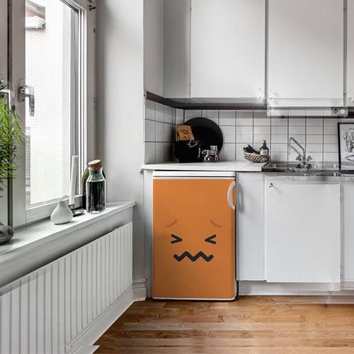 Petit frigo classique orné d'un sticker adhésif pour électroménager Smiley Tracas Orange dans une cuisine blanche