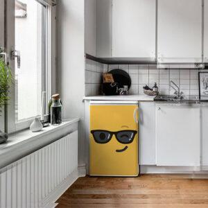 Lave vaisselle avec un sticker déco Smiley clin d'oeil jaune collé dessus