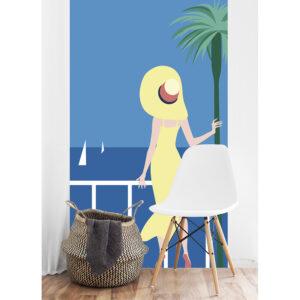Poster géant en intissé, panoramique, facile à poser, ambiance estivale, bord de mer, dame à la robe et au chapeau aux couleurs du soleil regardant l'horizon, fond ciel et mer bleu azur, palmier et voiliers.